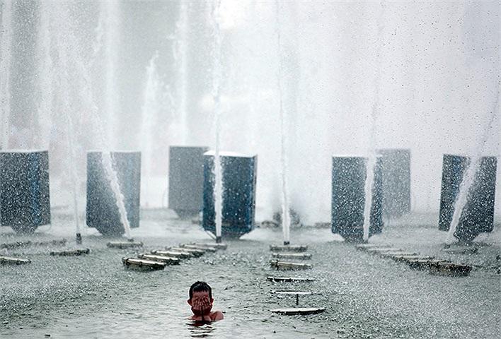 Bé trai tắm trong đài phun nước trong một công viên ở Moscow, Nga