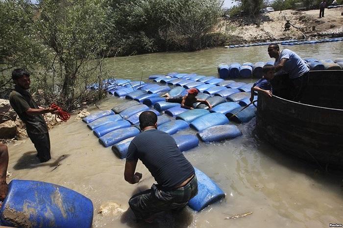 Những người đàn ông buôn lậu dầu từ Syria sang Thổ Nhĩ Kỳ ở sông Al-Assi, thị trấn Darkush Idlib