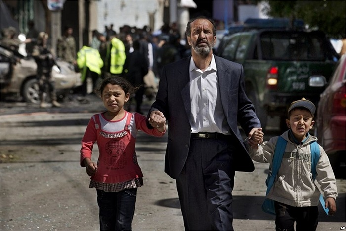 Người cha kéo hai con đi chỗ khác để khỏi nhìn cảnh đánh bom tự sát nhắm vào đoàn xe của binh sĩ NATO tại thủ đô Kabul, Afghanistan