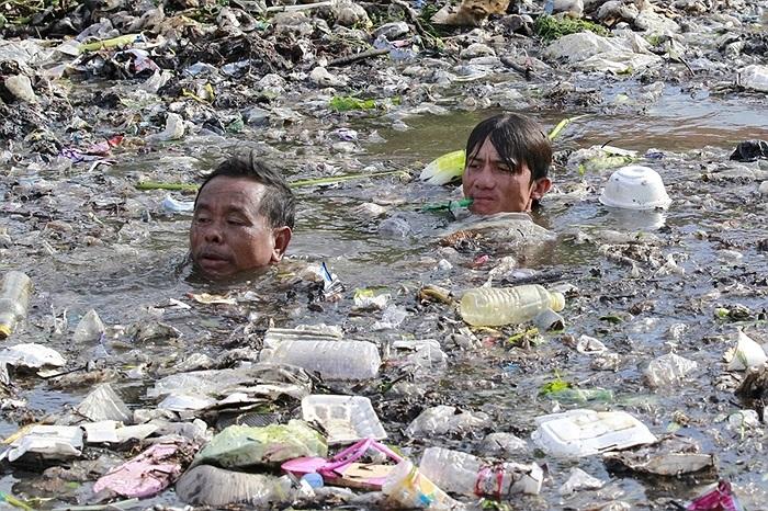 2 nhân viên cứu hộ lặn ngụp trong dòng nước bẩn tìm kiếm các nạn nhân trong vụ tai nạn ở Campuchia