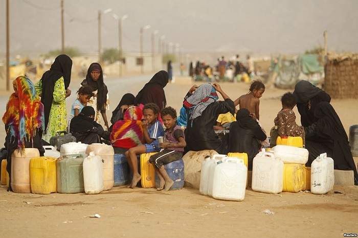 Phụ nữ và trẻ em Yemen đi hứng nước trong một trại dành cho những người tị nạn