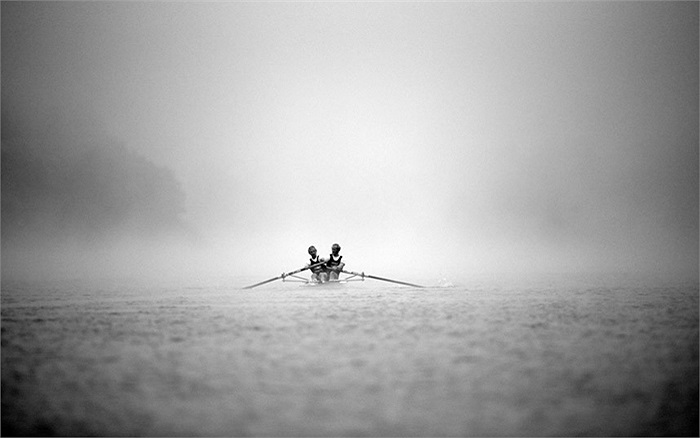 2 vận động viên chèo thuyền trên vùng nước đầy sương mù