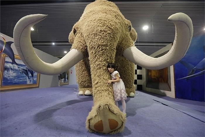Bé gái làm dáng cùng mô hình voi ma mút khổng lồ