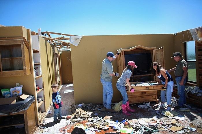 Một gia đình đang thu dọn đống đổ nát sau những trận lốc xoáy liên tiếp tại Oklahoma, Mỹ