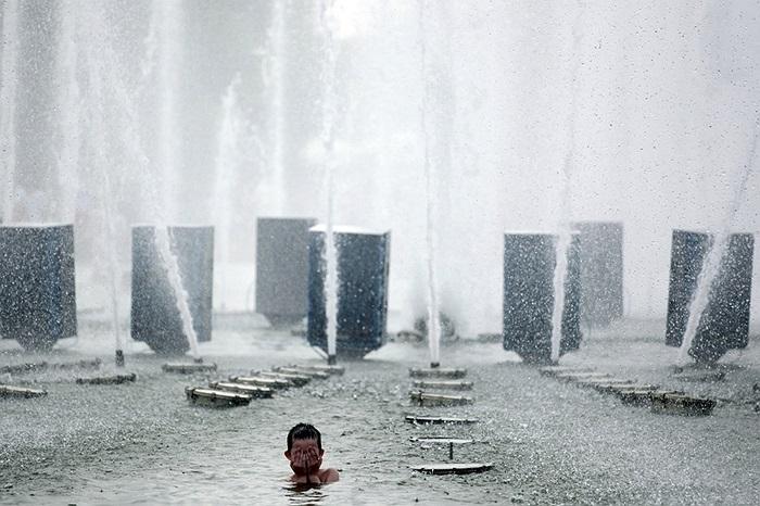 Đứa trẻ chơi đùa trong đài phun nước ở công viên Matxcơva, Nga