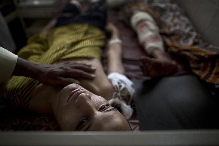 Một người đàn ông Pakistan động viên con trai bị thương trong vụ đánh bom liều chết tại nhà thờ Peshawar, Tây Nam đất nước