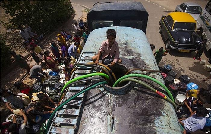 Cậu bé ngồi trên xe container cung cấp nước cho người dân của chính phủ ở New Delhi, Ấn Độ