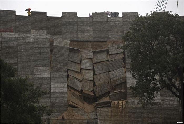 Một nhân viên kiểm tra quan sát bức tường bị bão đánh đổ ở Hong Kong