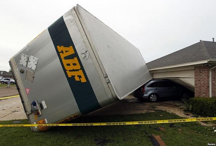 Xe chở hàng bị lốc xoáy thổi bay vào một căn nhà ở thành phố Cleburne, tiểu bang Texas, Mỹ, và đè lên chiếc xe của nhà dân