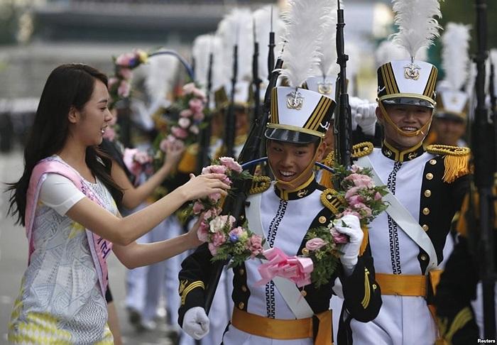 Sinh viên Học viện Hải quân Hàn Quốc vui cười nhận vòng hoa từ tay tân Hoa hậu Hàn Quốc 2013 trong một cuộc diễn hành kỷ niệm ngày Quân đội lần thứ 65 của Hàn Quốc ở trung tâm Seoul
