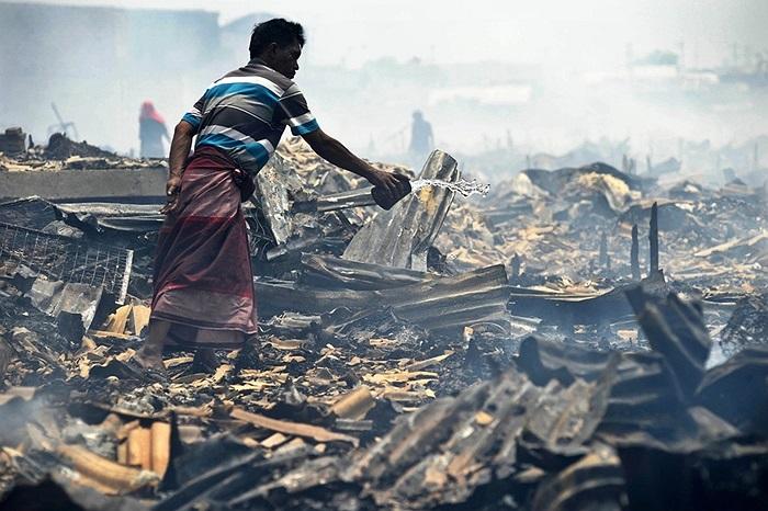 Người đàn ông dùng nước dập đám lửa cháy âm ỉ sau hỏa hoạn ở Jakarta, Indonesia
