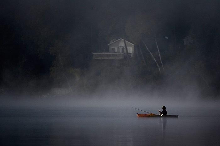 Một người đàn ông ngồi thuyền kayak đi câu cá giữa sương mù ở hồ Southwick, Mỹ