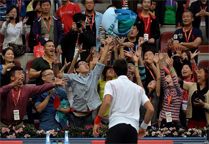 Vận động viên Novak Djokovic của Serbia ném khăn cho đám đông khán giả sau khi thắng trận đơn nam trước đối thủ Lukas Rosol của Cộng hòa Czech tại Giải quần vợt Trung Quốc mở rộng ở Bắc Kinh