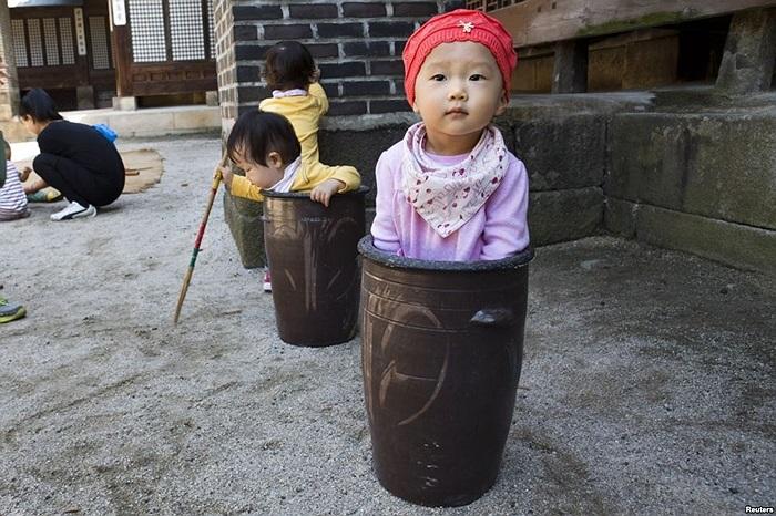 Bé Jung Ha-yoon, 2 tuổi, ngồi chơi trong một bình gốm cùng những em nhỏ khác trong Lễ hội ẩm thực truyền thống của giới quý tộc và hoàng gia, tổ chức tại Cung điện Unhyeon, Seoul