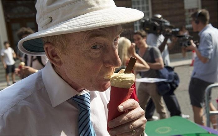 Phóng viên Nicholas Witchell của đài BBC thưởng thức ly kem trong khi đợi ở bên ngoài bệnh viện St Mary