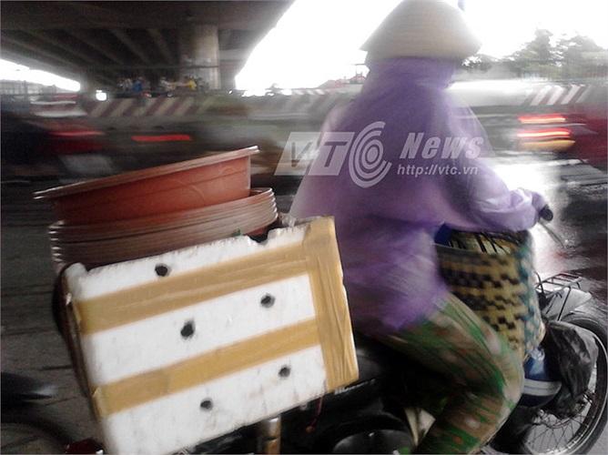 Chở thùng đá chứa cua biển, người phụ nữ vội vã chạy trốn mưa trên Đại lộ Nguyễn Văn Linh (Q.7).