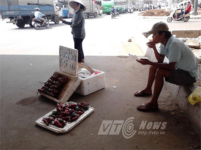 Người đàn ông ăn vội hộp cơm trưa, người phụ nữ vẫy tay mời đón khách đi đường ghé mua cua dưới chân cầu vượt Kha Vạn Cân (Q.Thủ Đức).