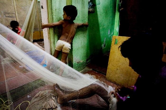 Một em nhỏ đang chơi bên cạnh người đàn ông chuẩn bị lưới đánh cá