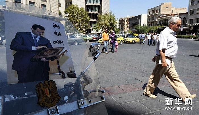 Ngày 4/9, một người đàn ông đi qua chiếc xe cảnh sát ở thủ đô Damascus, Syria