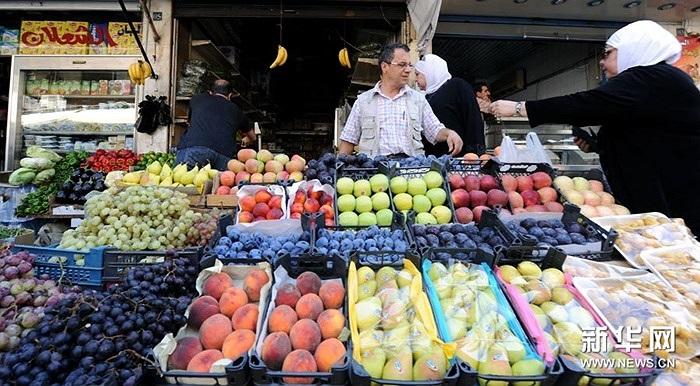 Một phụ nữ trước quầy bán hoa quả ở Damascus ngày 4/9