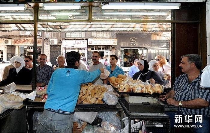 Người dân xếp hàng mua bánh trên phố Damascus hôm 4/9
