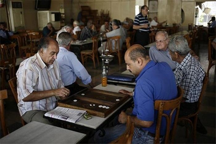 Hai người đàn ông thản nhiên chơi cờ trong quán cà phê