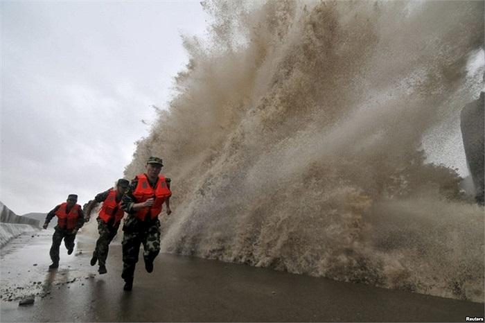 Lính biên phòng chạy qua sóng lớn do bão Fitow gây nên tại Ôn Lĩnh, tỉnh Chiết Giang, Trung Quốc