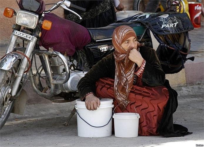 Người phụ nữ ngồi chờ đến lượt mình nhận phần ăn miễn phí ở thành phố Raqqa, phía đông Syria