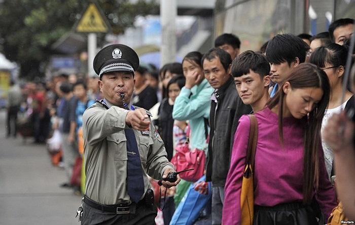 Bảo vệ giữ trật tự tại một trạm xe buýt bên ngoài nhà ga xe lửa của thành phố vào lúc cao điểm trong ngày cuối cùng của dịp lễ Quốc khánh của Trung Quốc ở Hợp Phì, tỉnh An Huy