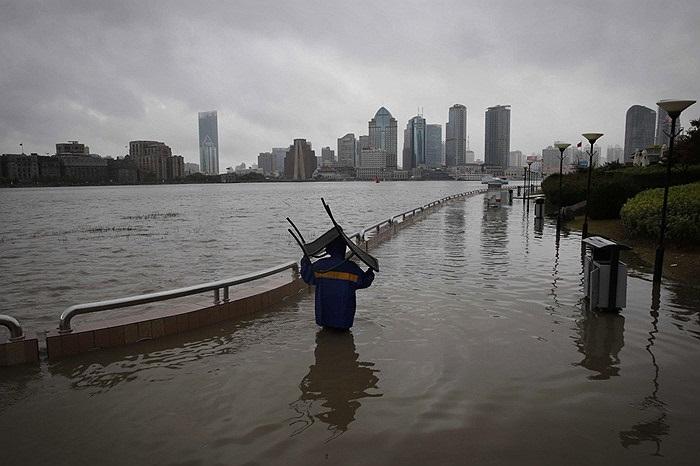 Người dân mang chiếc ghế qua vùng nước ngập ở Thượng Hải, Trung Quốc