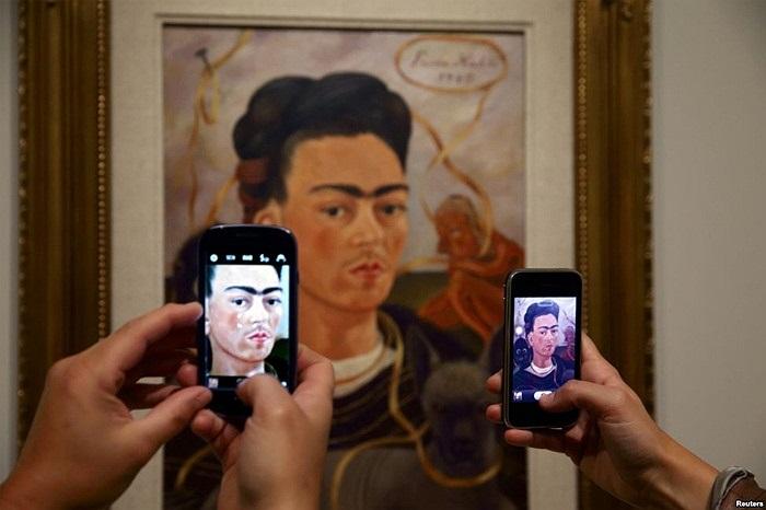 Khách tham quan chụp ảnh bức 'Tự họa với khỉ' của họa sĩ người Mexico Frida Kahlo triển lãm 'Frida Kahlo/Diego Rivera , Art in Fuson' tại bảo tàng Musee de l'Orangerie ở Paris
