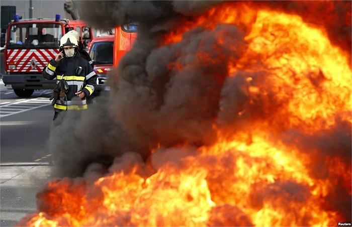 Lính cứu hỏa người Bỉ đứng sau đống lốp xe bốc cháy trong cuộc biểu tình của lính cứu hỏa đòi điều kiện làm việc tốt hơn ở trung tâm thủ đô Brussels