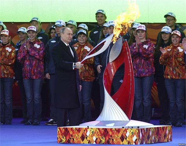Tổng thống Nga Vladimir Putin cầm ngọn đuốc Olympic được thắp lửa trong buổi lễ để đánh dấu khởi đầu hành trình rước đước Thế vận hội mùa đông Sochi 2014
