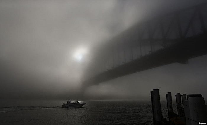 Một chiếc thuyền tại cầu Cảng Sydney đi qua màn sương mù dày đặc