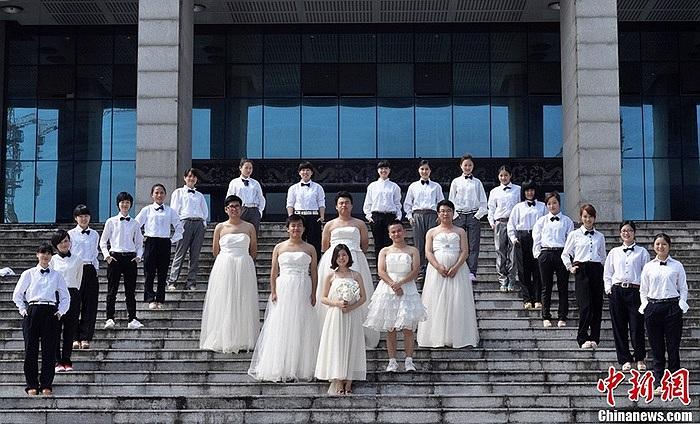 Nam sinh mặc váy cưới trắng, còn các bạn gái mặc complet, thắt nơ