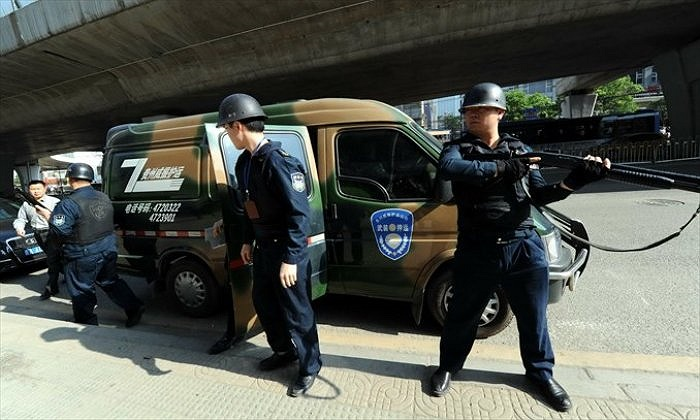 Được trang bị súng trường tự động, giữ đôi mắt quan sát khắp nơi khi các bọc tiền ra khỏi ngân hàng, lực lượng bảo vệ 141 của công ty Weizhen có nhiệm vụ bảo vệ xe chuyển tiền của ngân hàng từ Quý Dương (Quý Châu)