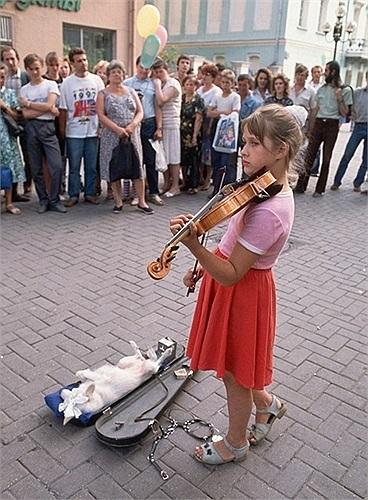 Cô bé chơi violon cùng với chú chó của mình trên đường phố Matxcơva