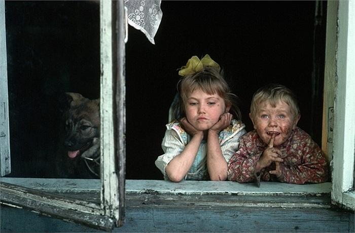 Hai đứa trẻ dơ bẩn, không được tắm rửa nhìn ngắm mọi thứ qua ô cửa sổ căn nhà trong khu thai thác mỏ ở Siberia
