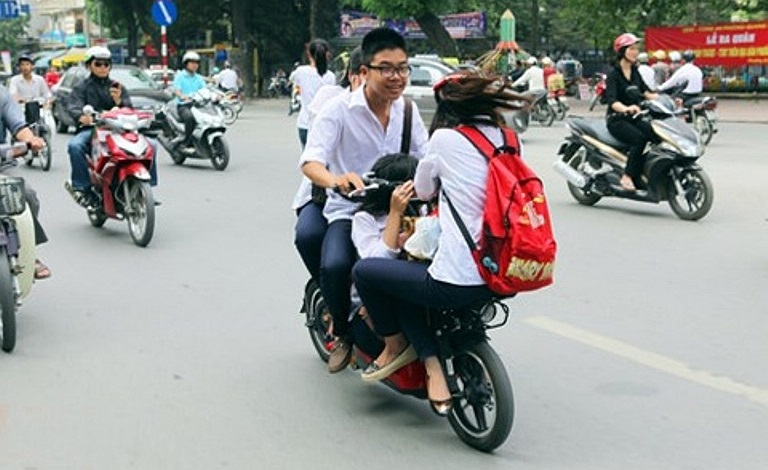 4 học sinh không đội MBH, ngồi nhồi nhét trên chiếc xe đạp điện. Ảnh chụp trên phố Tây Sơn, Hà Nội (Ảnh: Khám phá)