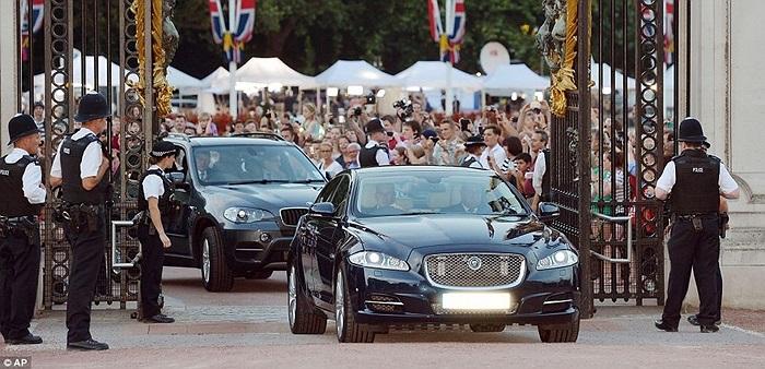 Một chiếc xe Jaguar tiến vào sân trước Cung điện Buckingham mang theo thông báo