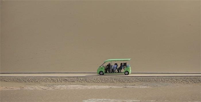 Một chiếc xe mang khách du lịch đến vùng ốc đảo, địa danh đã có từ thời nhà Hán của Trung Quốc
