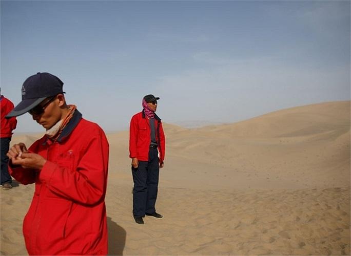 Những hướng dẫn viên du lịch mặc áo đỏ đặc trưng đứng đợi khách