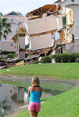 Cô gái đứng nhìn phần còn lại của khách sạn thuộc khu nghỉ mát Summer Bay Resort, gần Disney World ở Clermont, Florida, Mỹ sau khi hố tử thần xuất hiện