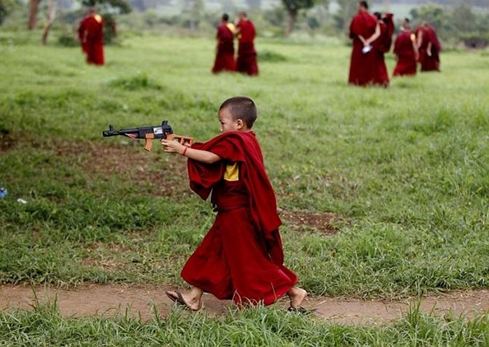 Một tu sĩ mới nhập môn chơi đùa với khẩu súng đồ chơi ở Gurupura, Ấn Độ