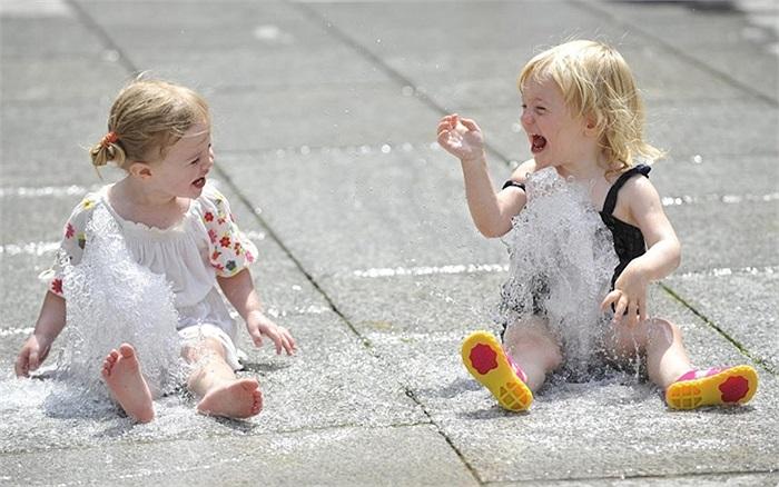 Hai bé gái vui đùa dưới vòi nước vỉa hè ở Học viện Hoàng gia Anh