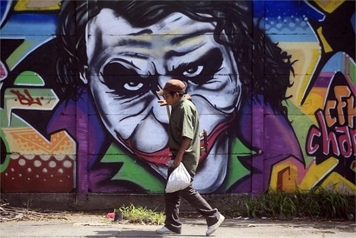 Người đàn ông đi qua bức tường vẽ nhân vật hề Joker nổi tiếng ở chợ Oriental, Nicaragua
