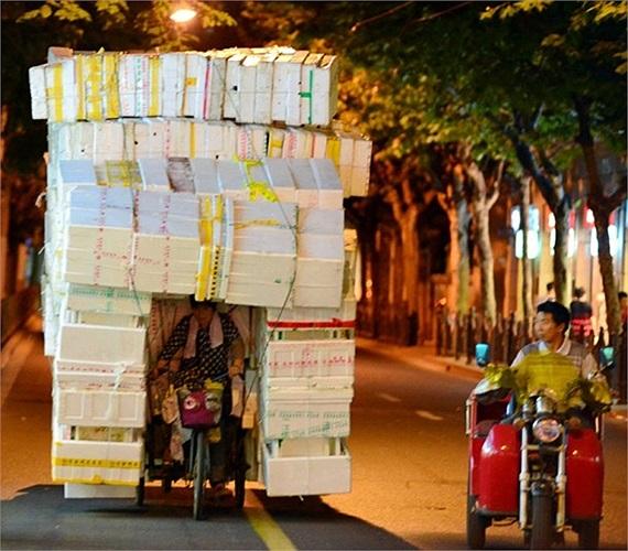 Người phụ nữ chở khối xốp rỗng khổng lồ bằng xe ba bánh trên đường Tây Nam Kinh ở Trung Quốc