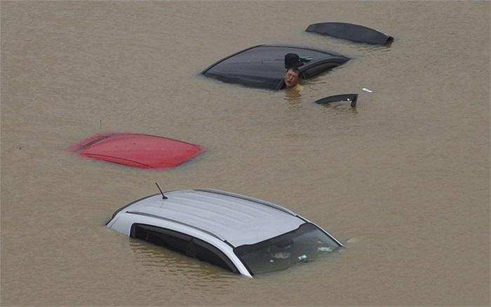 Người đàn ông cố gắng di chuyển chiếc xe bị ngập trong nước lũ sau khi mưa xối xả nhấn chìm khu vực trung tâm thủ đô Seoul, Hàn Quốc