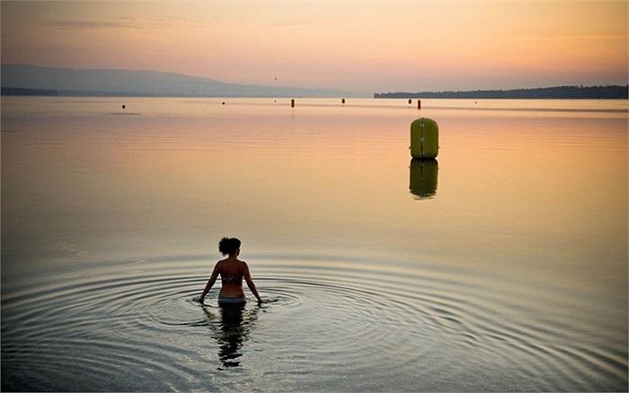 Người phụ nữ ngắm mặt trời mọc ở hồ Geneva, Geneva, Thụy Sĩ