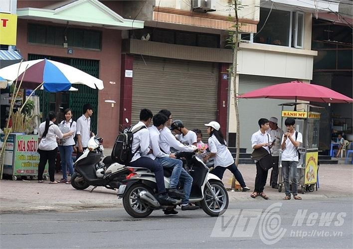 Học sinh kẹp ba, phóng nhanh, không đội mũ bảo hiểm sau giờ thi.